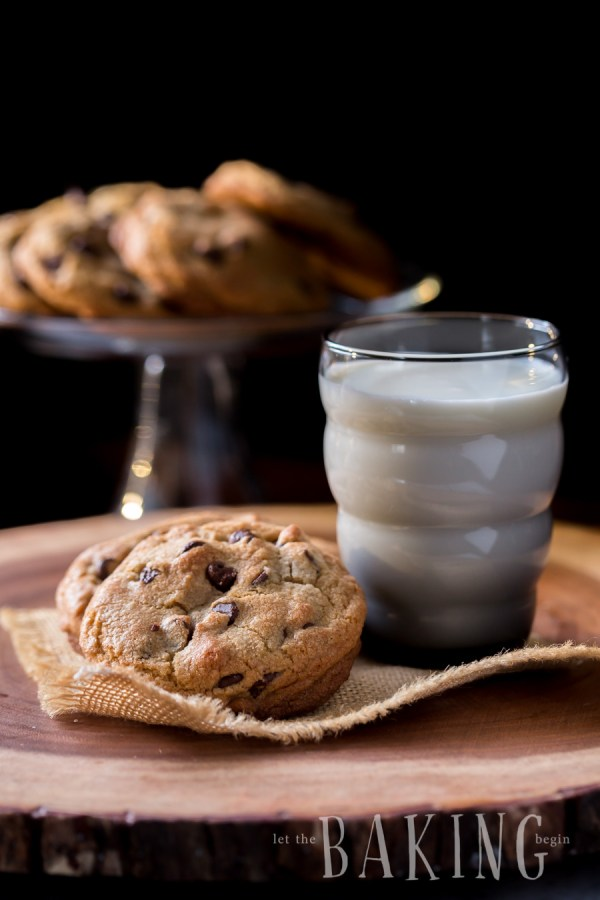 Chocolate chip cookies stacked on top of each next to a glass of milk.