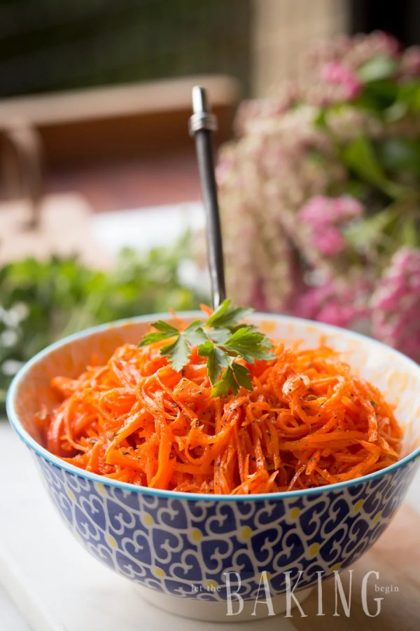 Spicy Korean carrots in a bowl with a metal spoon topped with parsley and grated black pepper.