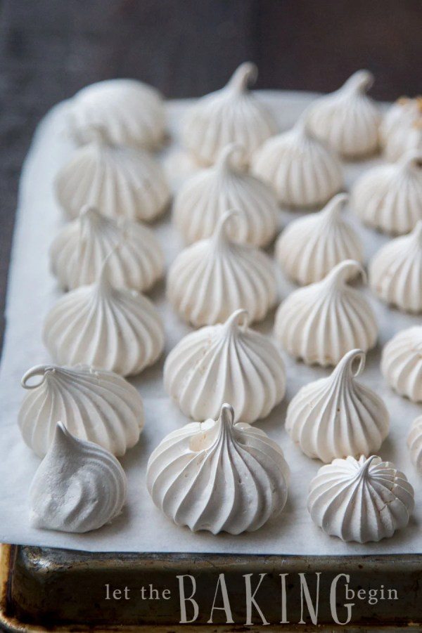 Meringue cookies on a parchment lined baking sheet.