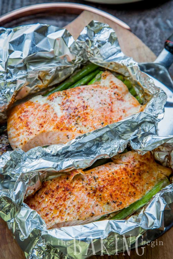 Two salmon and asparagus foil packets in a pan.