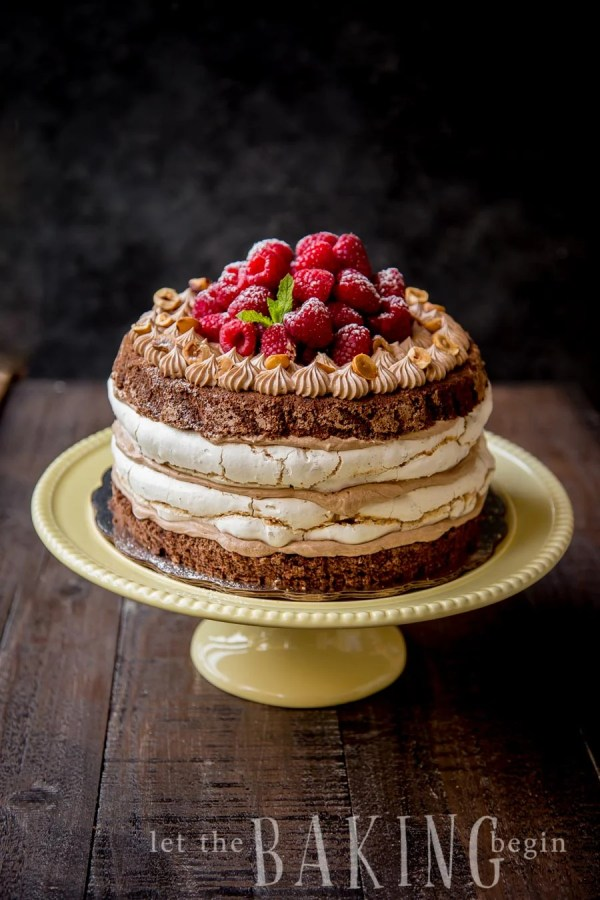 Hazelnut meringue Nutella cake on a yellow cake platter topped with raspberries.