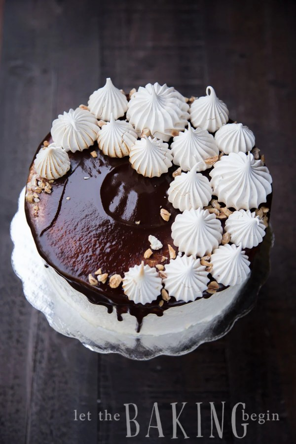 Kiev cake on a platter topped with chocolate, half meringues, and hazelnut.