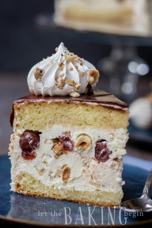 Kiev cake slice topped with chocolate, half meringue, and hazelnuts on a blue decorative plate.