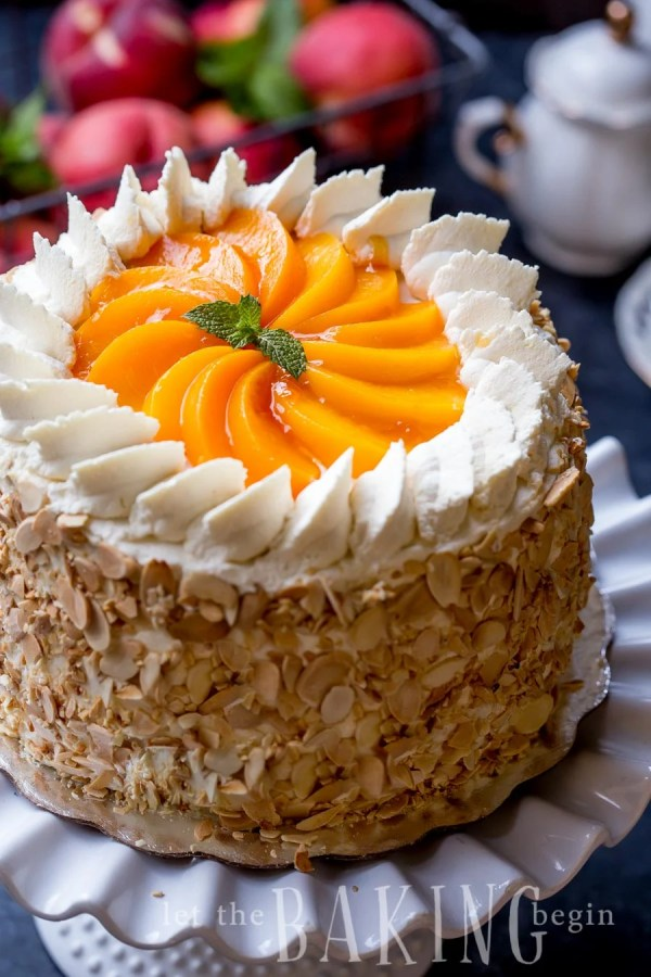Peached and cream cake on a cake platter tipped with peaches and whipped cream.