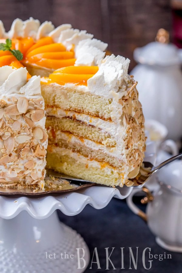 Peaches and cream cake on a cake platter with a slice being taken out.