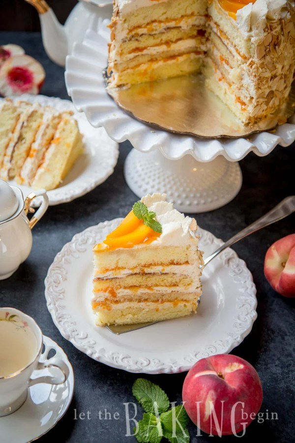 A slice of peached and cream cake on a plate next to a teacup and peaches.