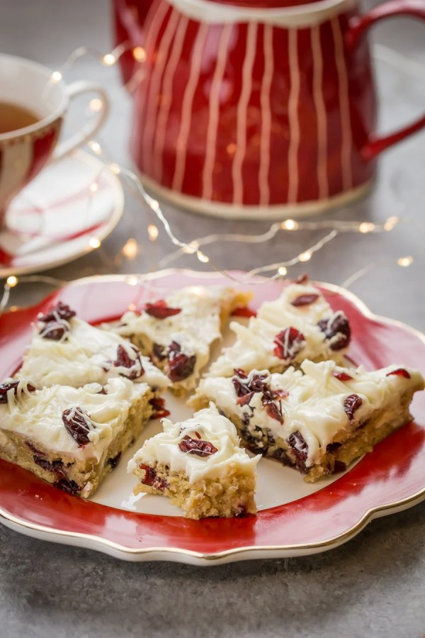Cranberry Bliss Bars on a plate with a tea kettle next to it.