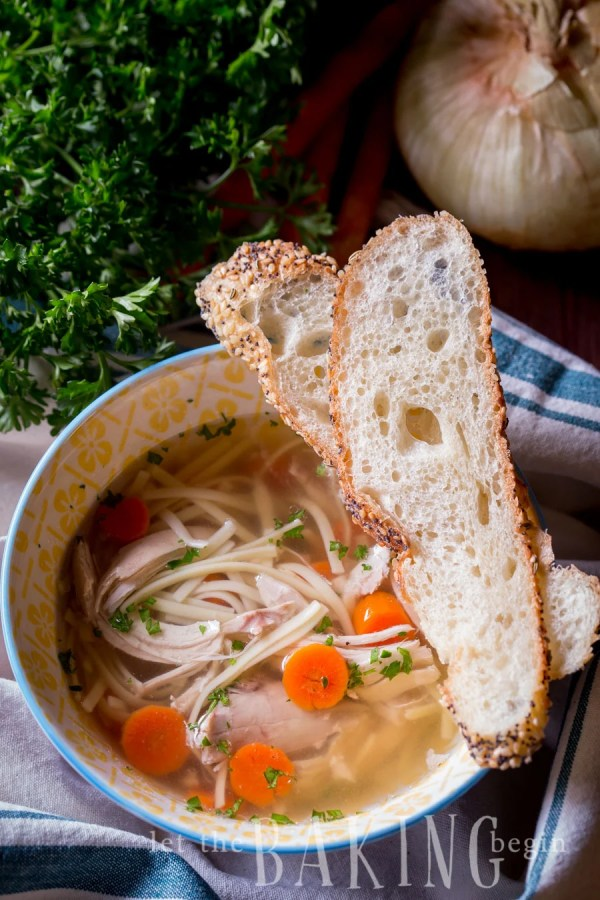 Instant pot chicken noodle soup in a bowl with bread slices.