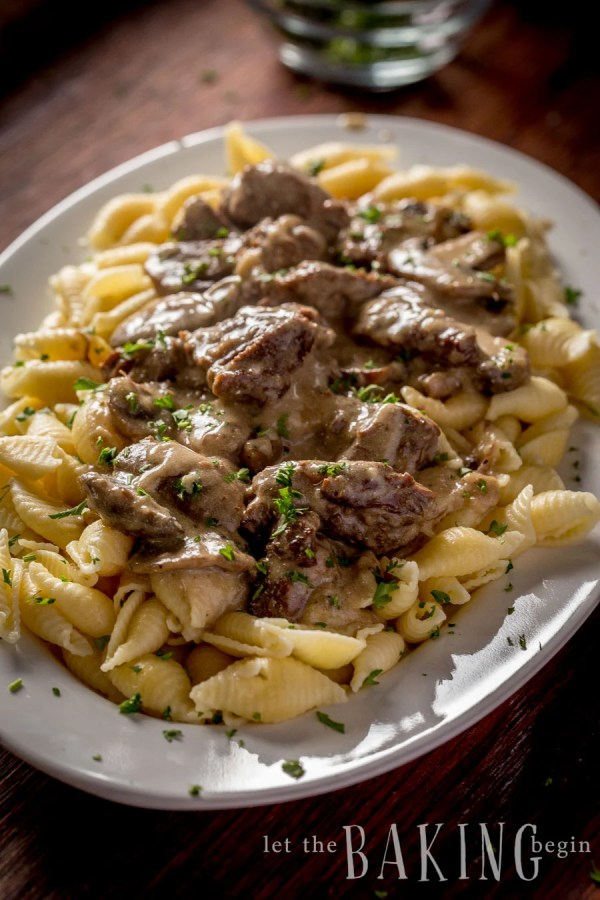Side view of beef stroganoff topped with fresh greens on a large decorative bowl.