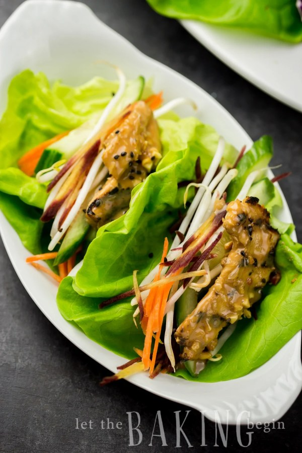 Two lettuce wraps with Thai chicken in peanut sauce on a plate.