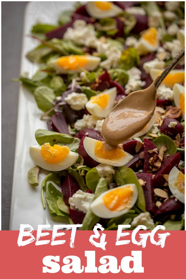 Beet Salad with Goat Cheese and Egg on a platter with Balsamic Dressing being added.