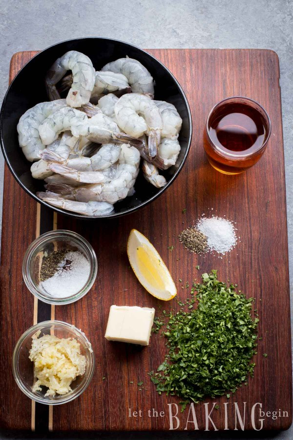 Raw shrimp in a black bowl with garlic, butter, salt and pepper, lemon, parsley, and oil on a wooden cutting board.