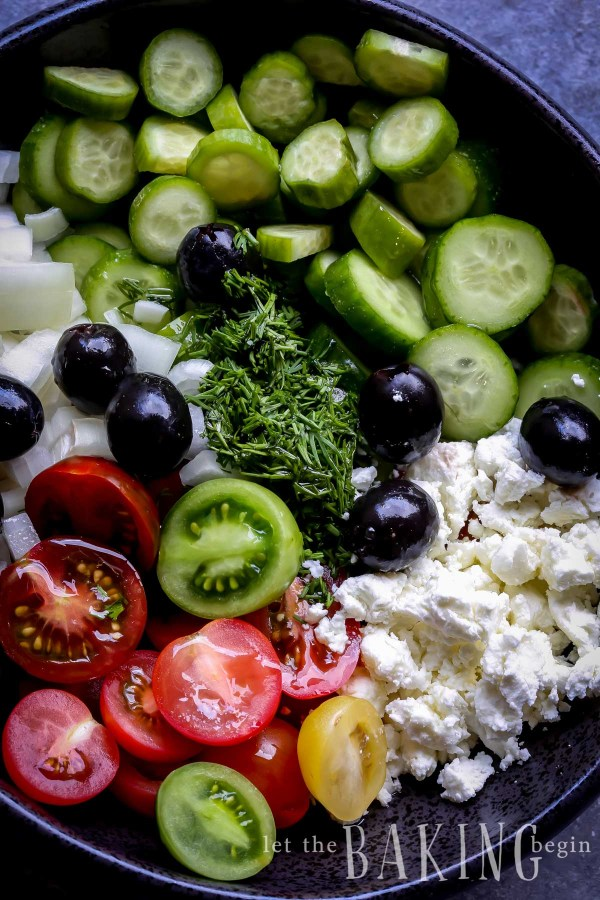 Cucumber salad topped with tomatoes, onions, olives, dill and goat cheese.