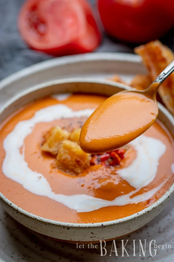 Tomato soup recipe in a white bowl with a spoonful of tomato soup.