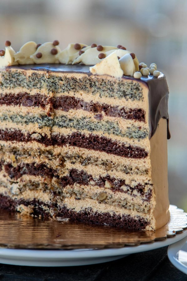 Russian Royal Cake is made with walnut, poppyseed, cherry and chocolate cake layers frosted with Dulce De Leche Buttercream then drizzled with Chocolate. Also known as Korolevskiy Cake this Russian Cake is voted the most favorite cake in my family.
