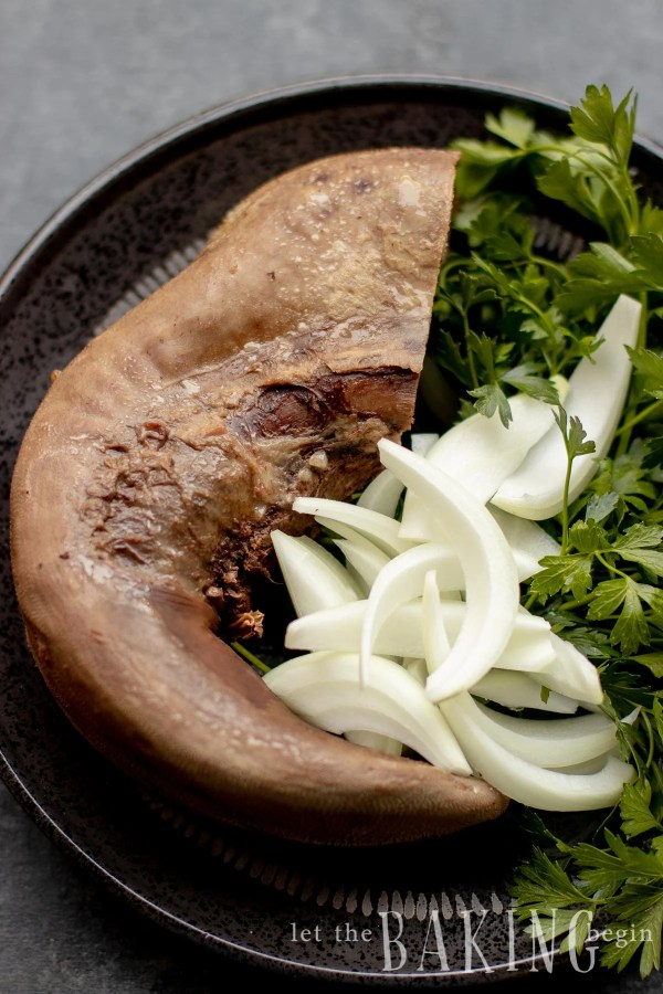 Cooked beef tongue with sliced onions and herbs
