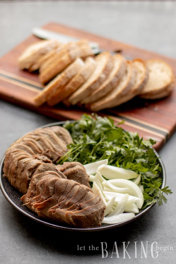 How to cook beef tongue. Sliced tongue on a platter with herbs, sliced onions and toast