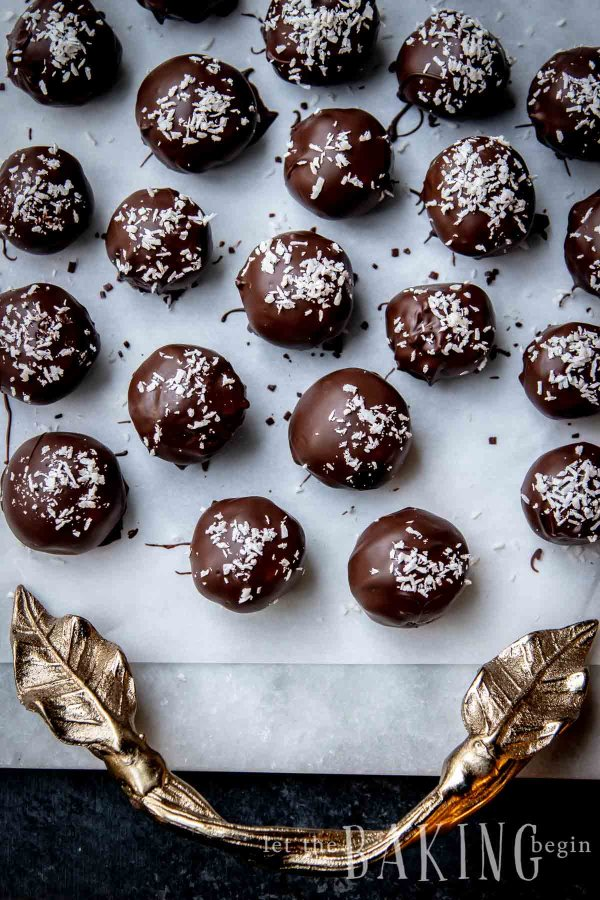 Chocolate coconut balls on white parchment paper.