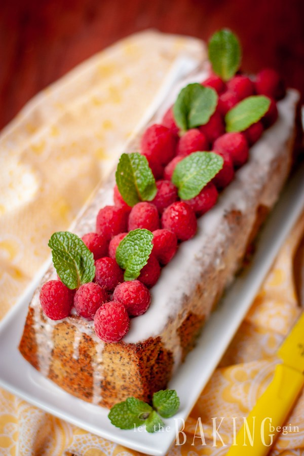 Full loaf of poppy seed cake with lemon glaze, raspberries, and mint on a white decorative plate.