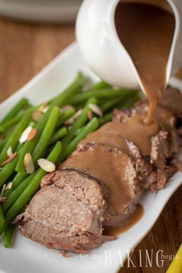 Green beans with almonds and roast with gravy on a decorative white plate.