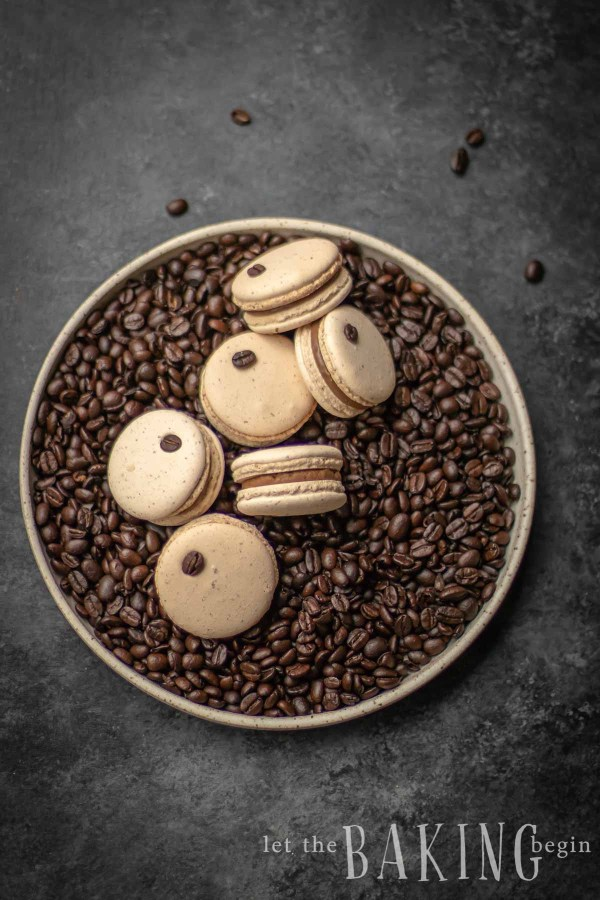 Coffee Macaron Recipe is a combination of a creamy coffee flavored white chocolate ganache and a basic macaron shell. They make amazing treats to go with coffee or tea, or as part of a potluck dessert tables at baby showers, birthdays or any other parties.
