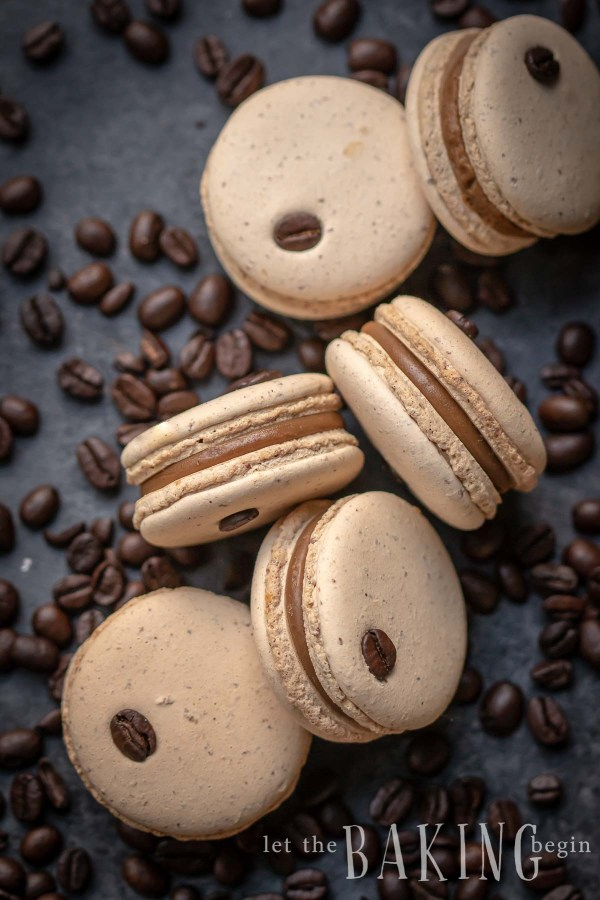Coffee Macarons with coffee ganache scattered with coffee beans.