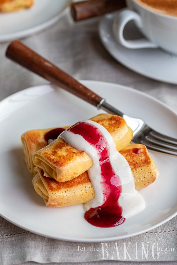Stack of cheese blintz on a white plate with a fork