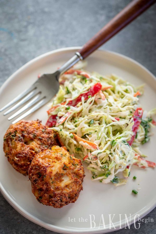 Crab cake recipe made on a plate with coleslaw on the side.