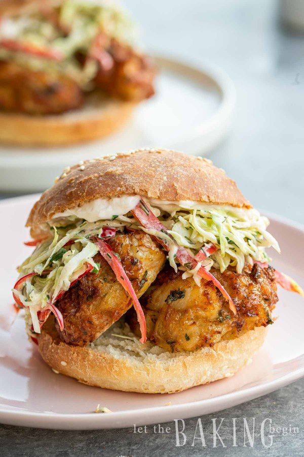 Two crab cakes in a bun with coleslaw