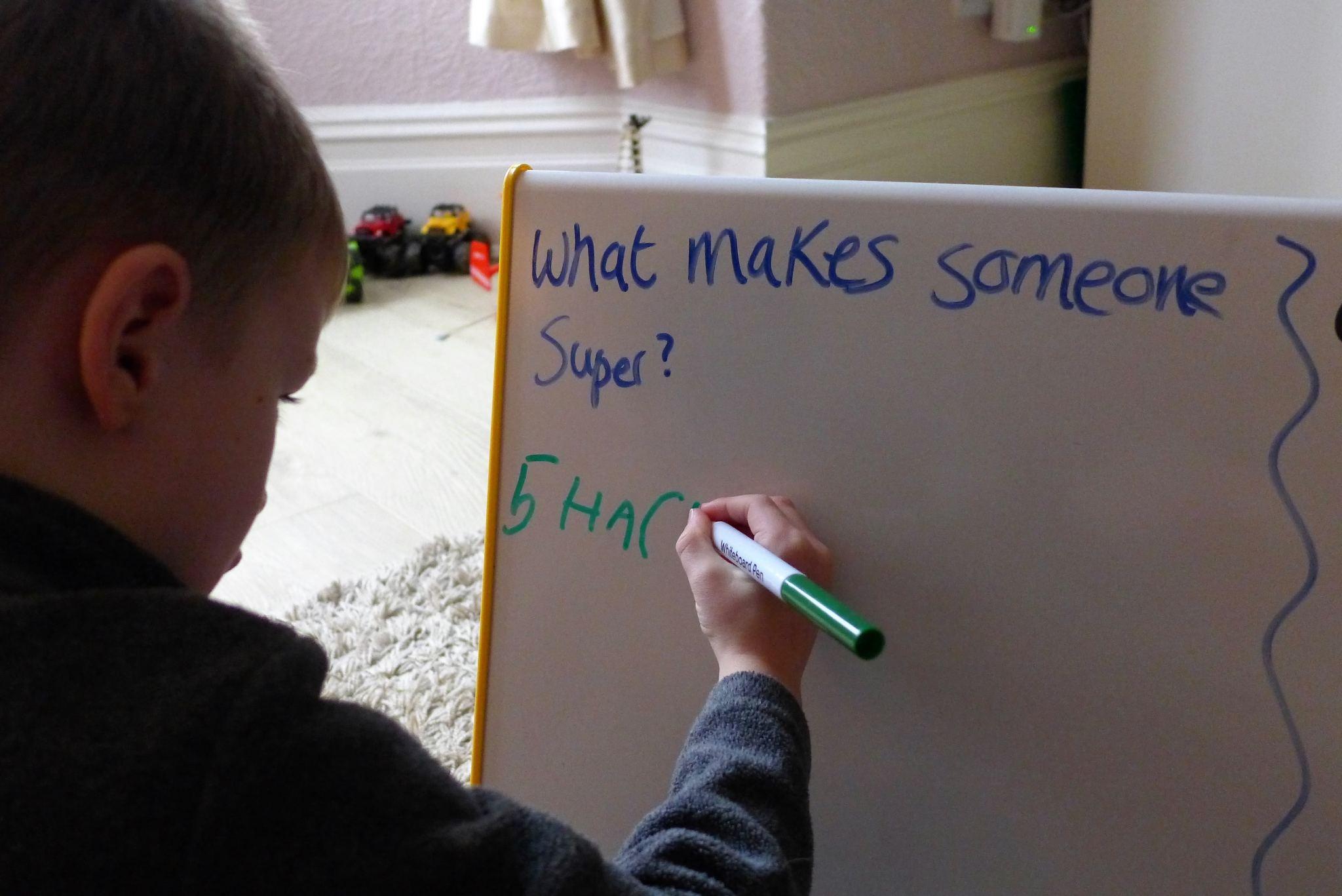 child writing on teacher board