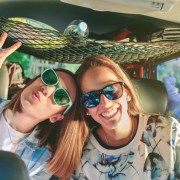 Two friends laughing and having fun inside of car