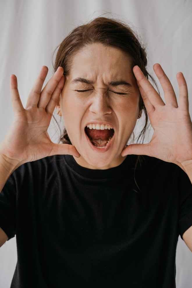 woman wearing a black t shirt shouting out loud