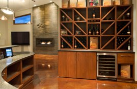 A more modern wine rack concept with mini-fridge below for cold storage and dark granite countertops for tastings.