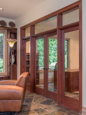 Transitional style glass doors embedded in wood molding leading to an office