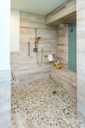Reclaimed wood, stone, and modern tile encompass this remodeled shower.