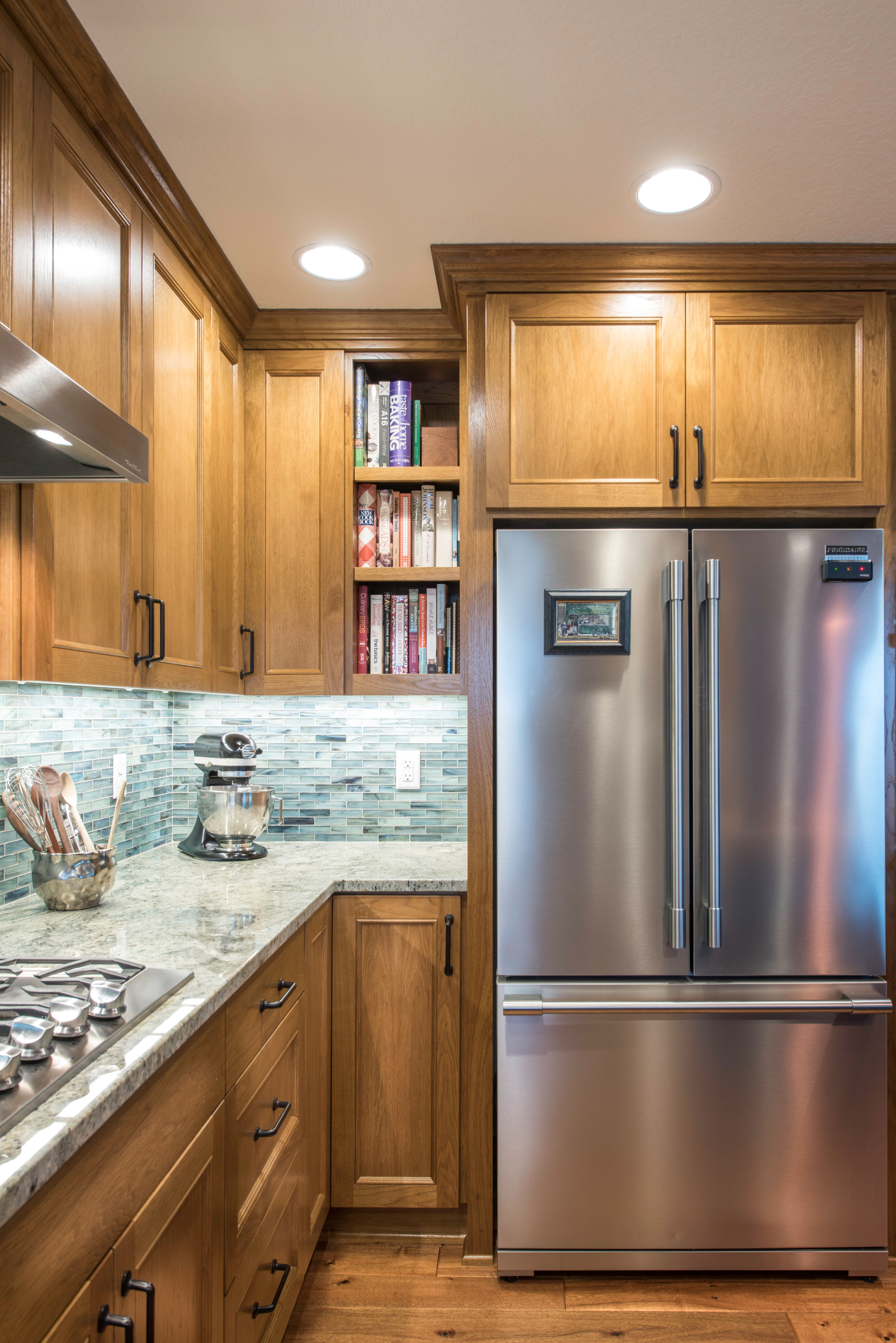 This modern and contemporary kitchen features blonde wood and a stainless steel refrigerator.