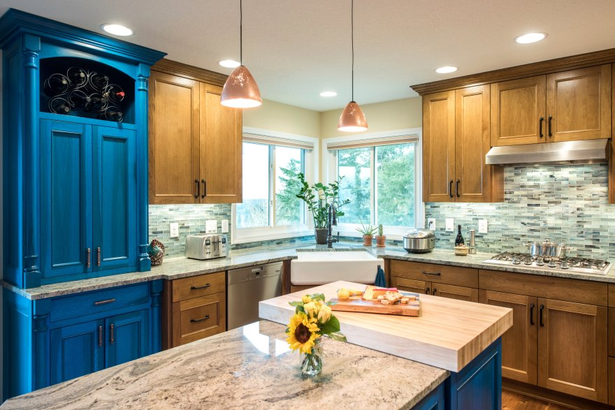A gorgeous Portland kitchen remodel with marble counters, blue accents, and modern pendant lights.