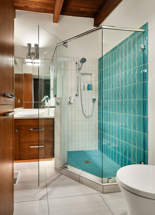 Bathroom remodel in Portland with blue green shower tile and light brown cabinets