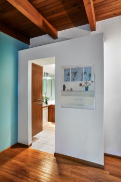 entry way to bathroom with wood floors baby blue walls and wood ceiling beams