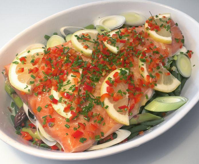 Ovnbagt lakseside med purløg, peberfrugt og citronskiver på bønner, asparges og porrer