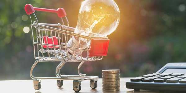 light bulb with stacks of coins and shopping cart