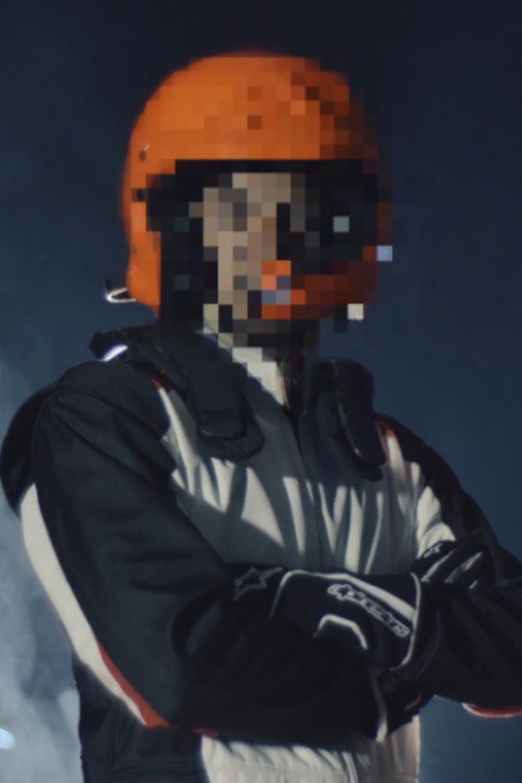 photographie d'un pilote de course avec le visage brouillé par des glitchs