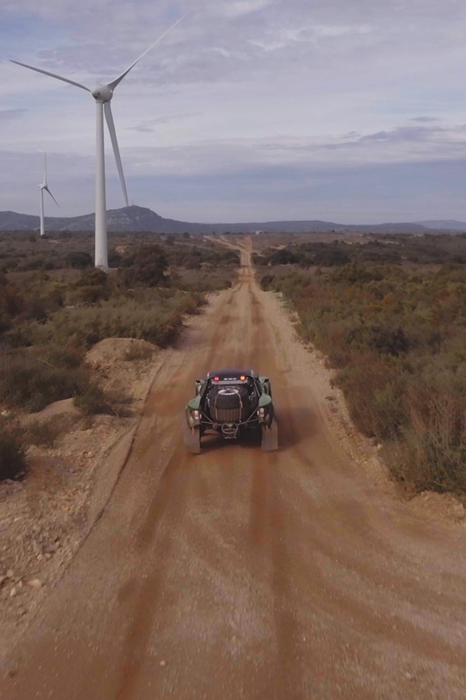 photo d'une voiture de rally dans le désert avec des éoliennes