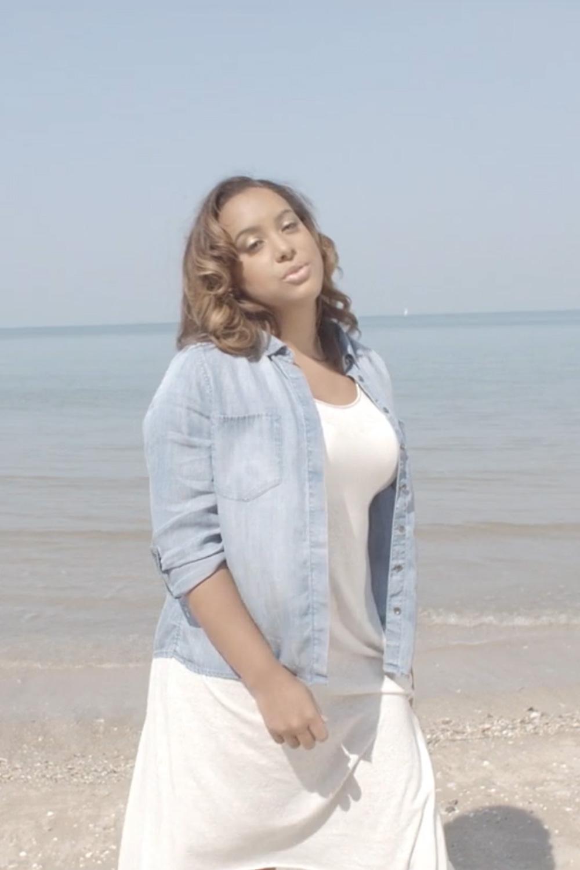 photographie de kim devant la plage en robe blanche