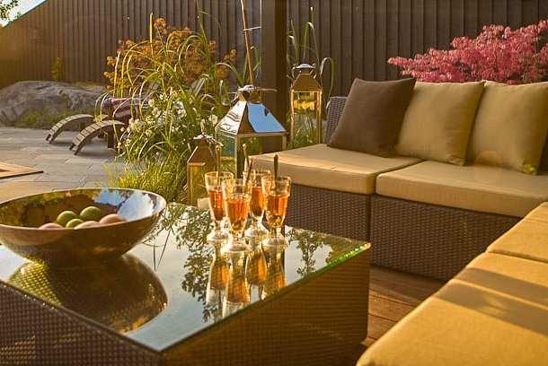 Stämningsfull uteplats med pergola ritad av trädgårdsarkitekt Ulrika Levin, Levins Trädgård & Design.