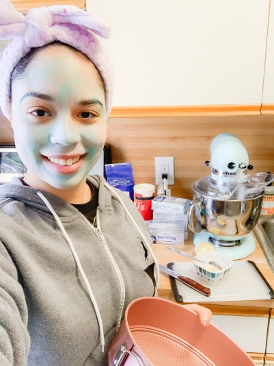 Becca from Levitate Beauty baking a cake while we're a skincare mask. Behind her is a kitchen aid mixer and ingredients for a cheesecake. A great way to practice self-care while self isolating.