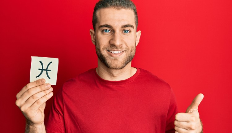 Young caucasian man holding paper with pisces zodiac sign smilin