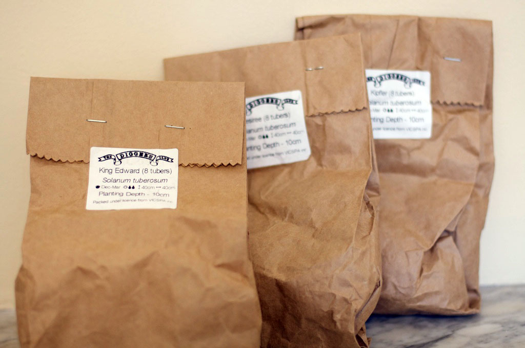 Three packets of seed potatoes, waiting for the new garden bed