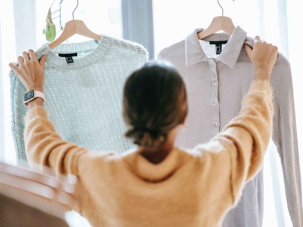 unrecognizable woman demonstrating clothes in store