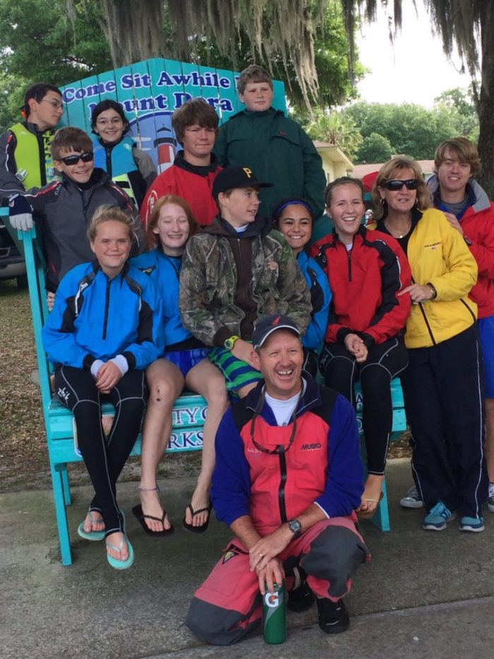 Group of sailors sit in a large chair at the Mount Dora Regatta